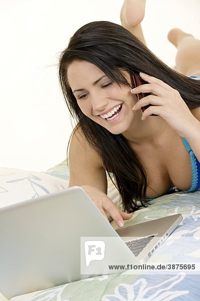 Beautiful Caucasian woman laying in bed working on laptop computer