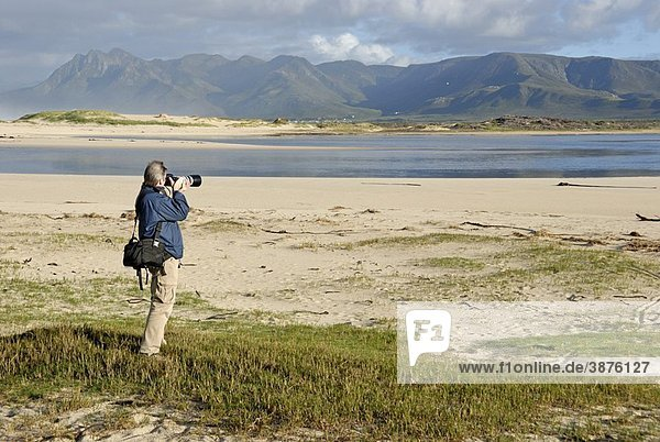 Man taking photograph of a landscape with telephoto in the morning  Flamingo lake estuary near Hermanus  South Western Cape  South Africa