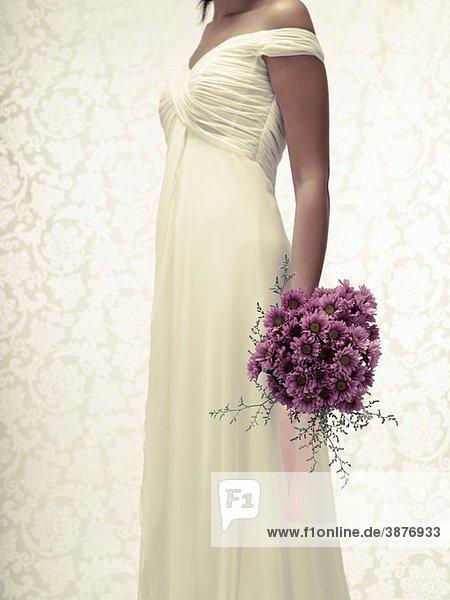 Bride in a white wedding dress holding a flower bouquet