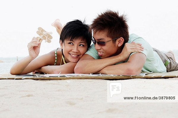 Young asian couple with girl holding a toy airplane