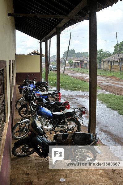 Geparkte Motorräder und Regen in San Rafael  Chiquitania  Departamento Santa Cruz  Bolivien  Südamerika