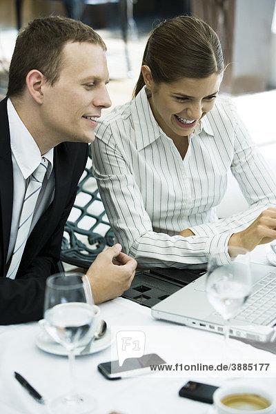 Geschäftsfreunde  die gemeinsam im Restaurant auf den Laptop schauen