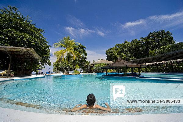 Junge Frau entspannt sich in einem Swimming Pool  Siladen Insel  Sulawesi  Indonesien  Südostasien