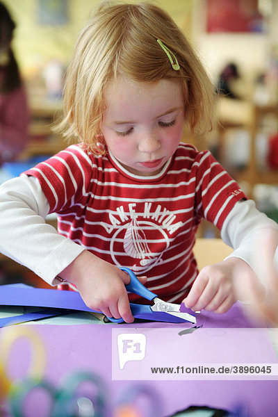 Rothaariges Mädchen beim Basteln im Kindergarten