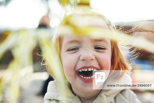 Lachendes Mädchen vor einer bemalten Fensterscheibe im Kindergarten Lachendes Mädchen vor einer bemalten Fensterscheibe im Kindergarten