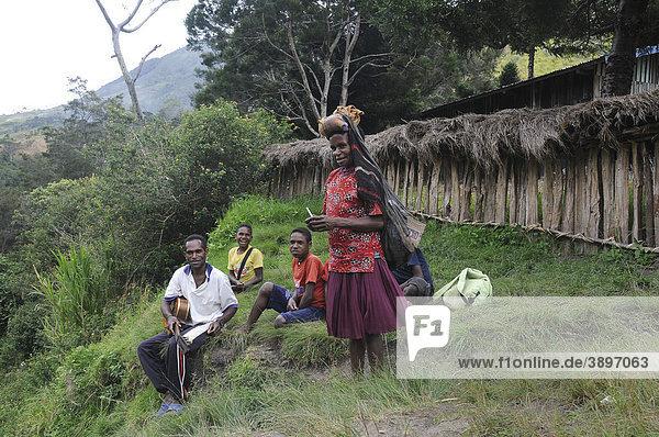 Danifrau kommt vom Feld und Jugendliche vom Volksstamm der Dani singen christliche Lieder mit Gitarrenbegleitung  Kurima  Baliem Tal  Irian Jaya  Indonesien  Südostasien  Asien