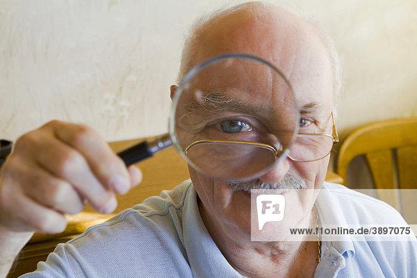 Rentner blickt durch eine Lupe