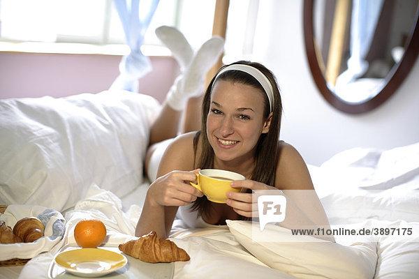 Frau bei Frühstück im Bett