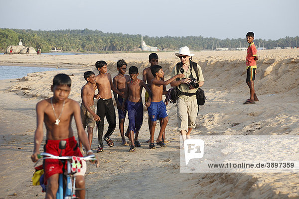 Photographer being accompanied by Indian children  Poovar River  Puvar  Kerala  South India  India  Asia