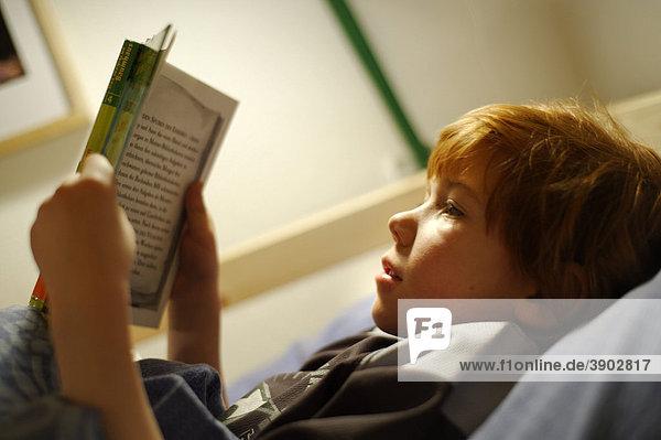 Kind  Junge beim Lesen im Bett