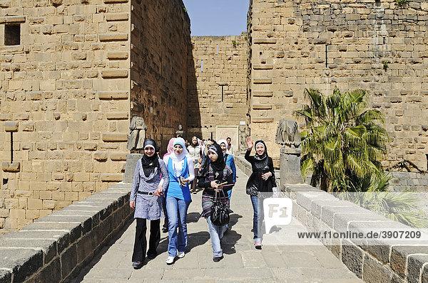 Junge Frauen mit Kopftuch am Eingang  römisches Theater in Bosra  Syrien  Asien