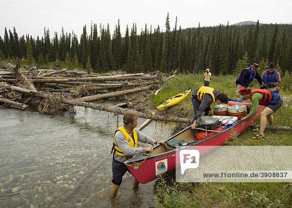 Männer und Frauen portagieren  ziehen ein Kanu über Land  umgehen ein Hindernis aus verkeilten Baumstämmen  oberer Liard River Fluß  Yukon Territory  Kanada