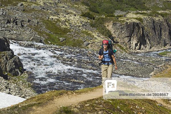 Junge Frau mit Rucksack wandert auf dem historischen Chilkoot Pass  Chilkoot Trail  Crater Lake dahinter  alpine Tundra  Yukon Territorium  British Columbia  BC  Kanada