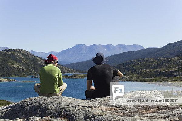 Junge Frau und Mann  Wanderer  rasten  genießen Blick auf Deep Lake  historischer Chilkoot Pass  Chilkoot Trail  Yukon Territorium  British Columbia  BC  Kanada