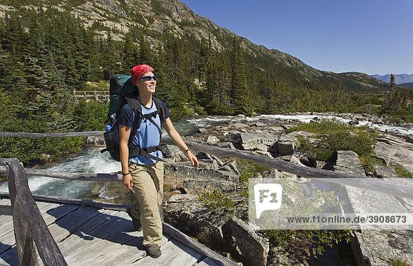 Junge Frau beim Wandern  beim Überqueren einer Holzbrücke  Wanderin mit Rucksack  historischer Chilkoot Pass  Chilkoot Trail  in der Nähe des Deep Lake  Yukon Territorium  British Columbia  BC  Kanada