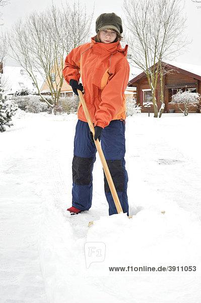 Mädchen schiebt Schnee vom Gehweg