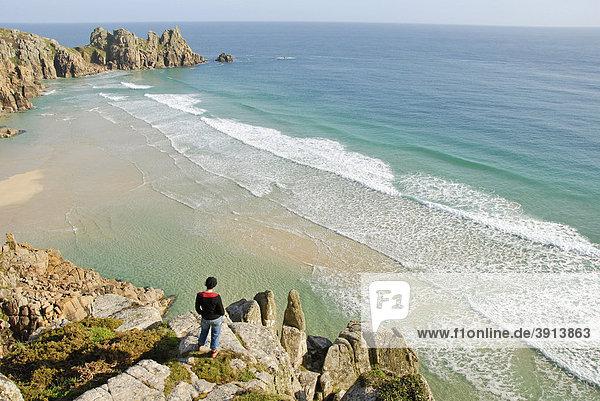 Frau schaut auf Wellen und Strand  Aussichtspunkt  Porthcurno Beach  Pednvounder Beach  Logan Rock  Südküste  Cornwall  England  Großbritannien  Europa