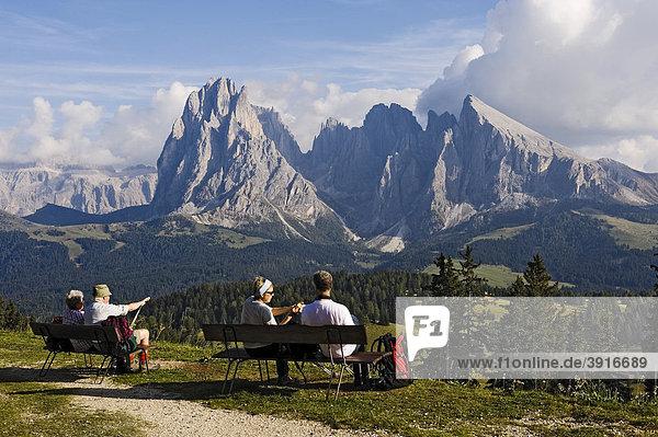 Wanderer blicken über die Seiser Alm auf den Langkofel und Plattkofel  Dolomiten  Südtirol  Italien  Europa