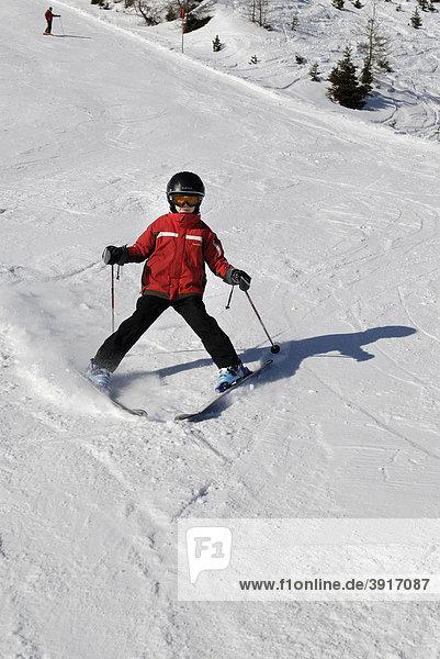 Kind beim Ski fahren  Abfahrt  Piste mit Helm  Sicherheit