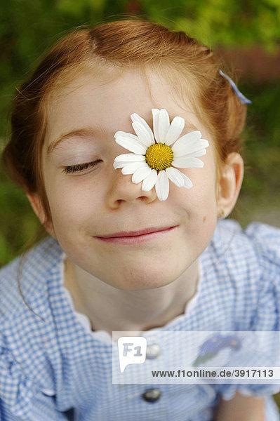 Mädchen mit Blume  Margerite  im Gesicht  Flower Power