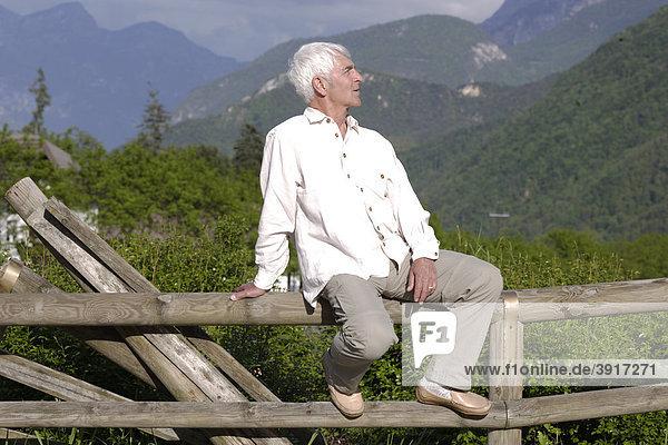 Senior sitzt auf einem Holzzaun  Norditalien  Europa  Rapallo  Dolomiten