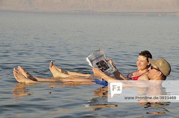 Touristen lesen Zeitung im Toten Meer bei Suwaymah  Jordanien  Naher Osten  Orient