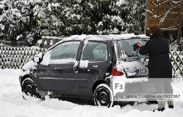 Frau kratzt Autoscheiben frei von Schnee und Eis