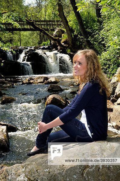 Junge Frau sitzt an einem Wasserfall