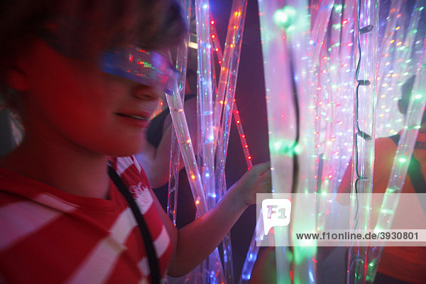 Boy in a maze  labyrinth made of colorful illuminated light rods  at a fair
