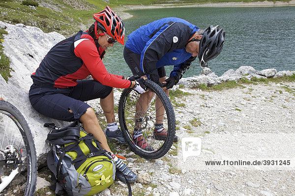 Mountainbike-Fahrerin und Fahrer mit Reifenpanne reparieren Vorderrad