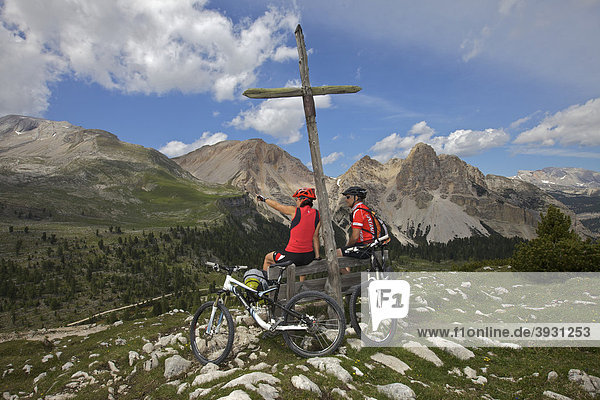 Mountain bike riders having a rest stop on a wooden bench in front of a wooden cross on the Limo Pass in Fanes-Sennes-Prags Nature Park  Trentino  Alto Adige  Italy  Europe