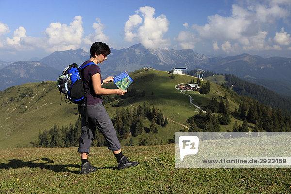 Wanderin blickt auf Wanderkarte auf der Alm  Zwieselalm  Salzkammergut  Oberösterreich  Österreich  Europa