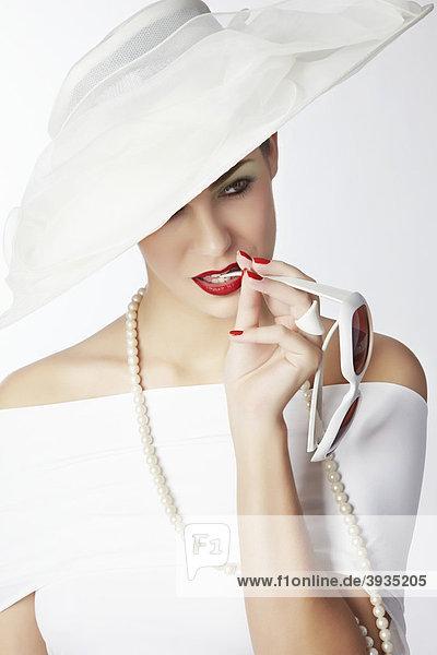 Portrait einer jungen Frau mit weißem Sommerhut  weißem Kleid und Perlenkette  beißt auf den Bügel einer weißen Sonnenbrille
