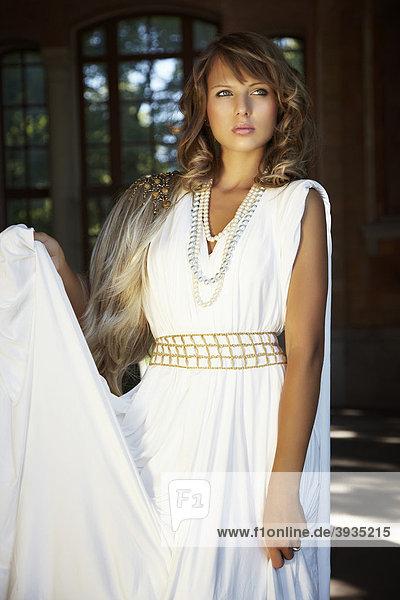 Portrait einer jungen blonden Frau in einem weißen langen Kleid
