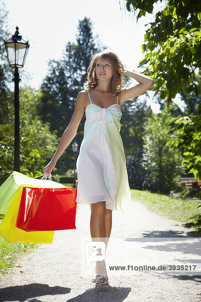 Young woman wearing a summer dress  holding shopping bags while running happily through a park
