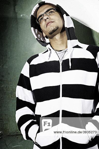 Portrait eines jungen Mannes mit Kapuzenjacke stehend vor einem alten Stahltor  den Blick nach oben abgewandt  Jugendlicher  cool