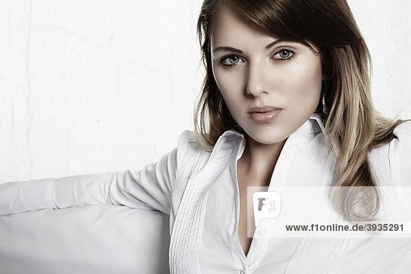 Portrait einer jungen Frau  sitzend auf einer weißen Couch  direkter Blick