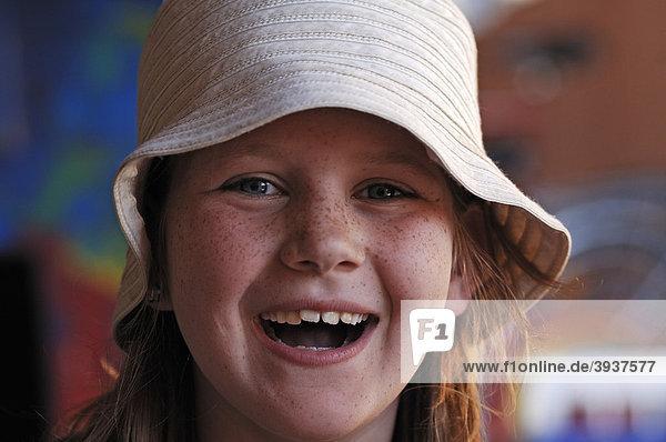 Portrait eines kleinen lachenden Mädchens mit Sommersprossen und mit weißem Hut