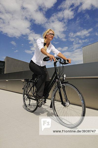 Junge Frau mit Fahrrad vor BMW-Welt  München  Bayern  Deutschland  Europa