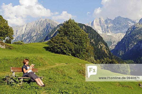 Frau liest ein Buch auf einer Bank mit Blick vom Bergdorf Soglio auf die Bondasca-Gruppe mit Sciora  Piz Cengalo und Piz Badile  Wanderweg Via Bragaglia und Sentiero Panoramico  Val Bregaglia  Tal des Bergell  Engadin  Graubünden  Schweiz  Europa