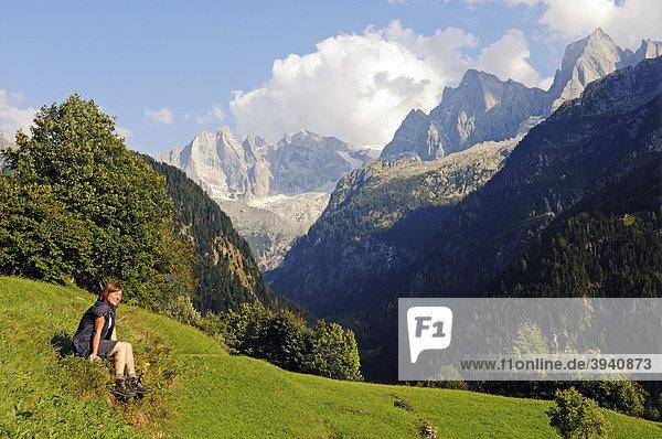 Frau sitzt im Gras mit Blick vom Bergdorf Soglio auf die Bondasca-Gruppe mit Sciora  Piz Cengalo und Piz Badile  Wanderweg Via Bragaglia und Sentiero Panoramico  Val Bregaglia  Tal des Bergell  Engadin  Graubünden  Schweiz  Europa