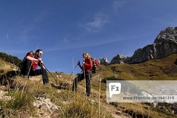 Wanderer  Frau und Mann  Tourenrucksack und Trekkingstöcke  rasten beim Aufstieg zur Heidachstellwand  2192m  Rofan  Achensee  Tirol  Österreich  Europa