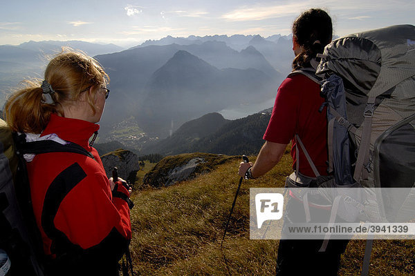 Wanderer  Frau und Mann mit Tourenrucksack und Trekkingstöcken auf dem Gipfel der Heidachstellwand  2192m  mit Blick in das Inntal und an den Achensee mit Maurach und ins Karwendel  Rofan  Achensee  Tirol  Österreich  Europa