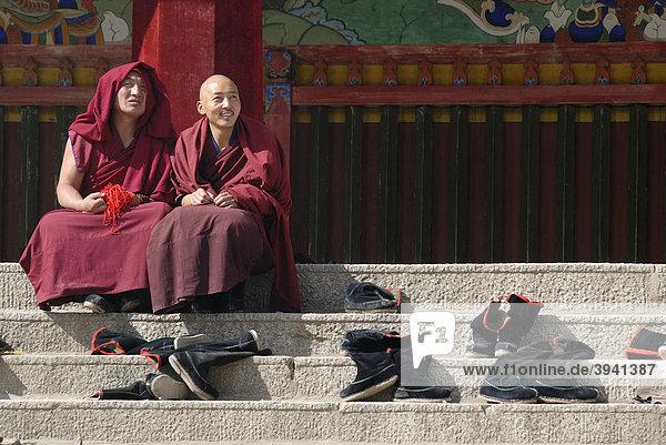 Tibetische Mönche in Mönchsrobe des Gelukpaordens sitzen neben ausgezogenen Mönchsstiefeln auf den Treppen vor der Versammlungshalle  tibetisch Dukhang  des Kloster Labarang  Xiahe  Gansu  China  Asien