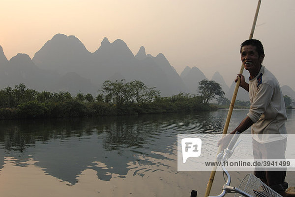 Bambusfloß mit altem chinesischem Mann mit Stake auf dem Yulong Fluss in der Karstfelsenlandschaft bei Yangshuo  Guilin  Guangxi  China  Asien
