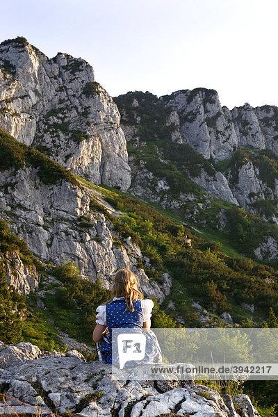 Junges Mädchen in bayerischer Tracht sitzt an einem Berghang an der Kampenwand  Chiemgau  Oberbayern  Bayern  Deutschland  Europa