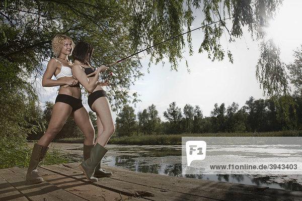 Zwei junge Frauen beim Angeln an einem See