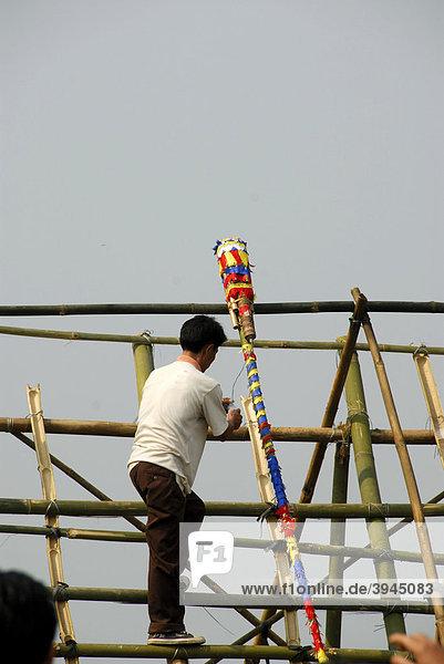 Mann legt bunt geschmückte Rakete aus Bambus auf Abschussrampe  Pi Mai  Laotisches Neujahrsfest  Volksfest  Phongsali Stadt  Phongsali Provinz  Phongsaly  Laos  Südostasien  Asien