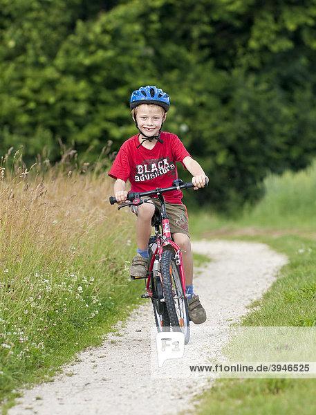 Ein Junge  7 Jahre  mit Fahrrad  auf einem Feldweg