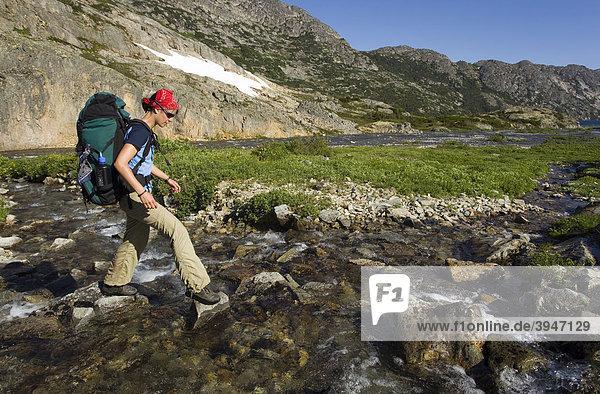 Junge Wanderin mit Rucksack überquert einen Bach  historischer Chilkoot Pfad  Chilkoot Pass  nahe des Happy Camp  alpine Tundra  Yukon Territory  British Columbia  B.C.  Kanada
